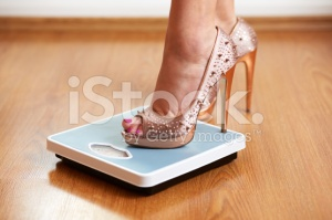 stock-photo-40180868-female-feet-in-golden-stilettos-on-a-weight-scale